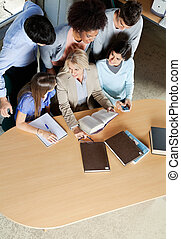 Teacher Discussing With Students At Desk In Classroom