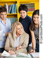 Teacher Discussing With Students At Table In College Library