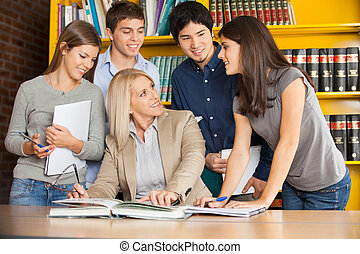 Teacher Discussing With Students At Table In University Library