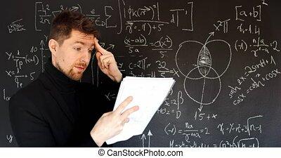 Teacher drawing mathematical formulas on black chalk board closeup