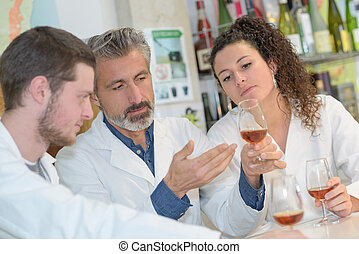 Teacher examining glass of cognac with students