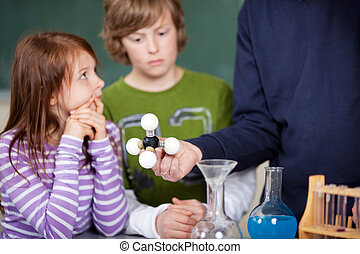 Teacher explaining an atomic model to two attentive young...