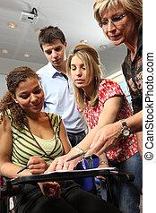 Teacher explaining work to teenage pupils