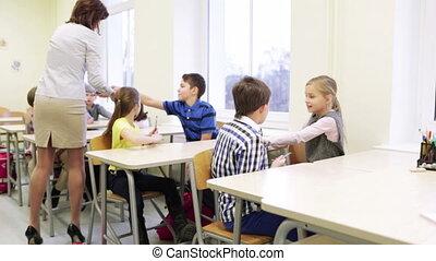 teacher giving pens to school kids in classroom - education,...