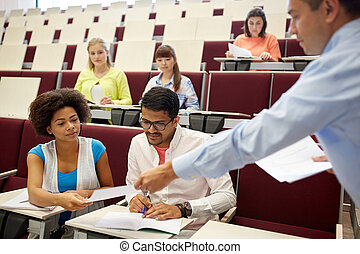 teacher giving tests to students at lecture