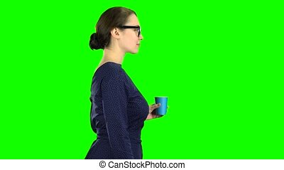 Teacher goes and drinks water from the glass. Green screen -...