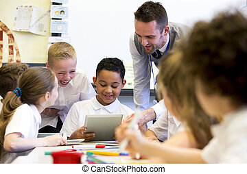 Teacher Happy at School - A male teacher sits supervising a...