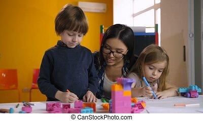 Teacher helping class of preschool kids to draw