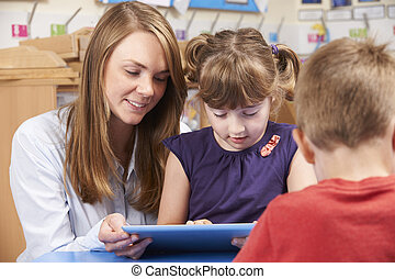 Teacher Helping Elementary School Pupil Use Digital Tablet