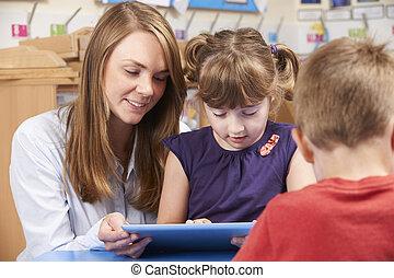 Teacher Helping Elementary School Pupil Use Digital Tablet
