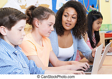 Teacher Helping Female Elementary Pupil In Computer Class