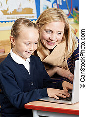 Teacher Helping Female Elementary School Pupil In Computer Class