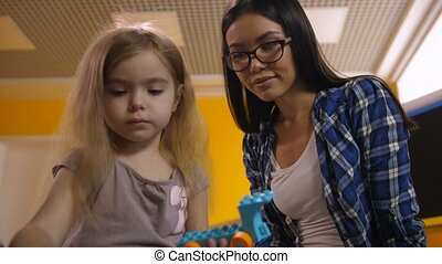 Teacher helping girl to create toy from constructor