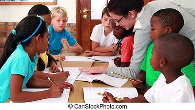 Teacher helping her pupils during class in elementary school