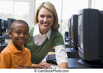 Teacher helping kindergarten children learn how to use computers