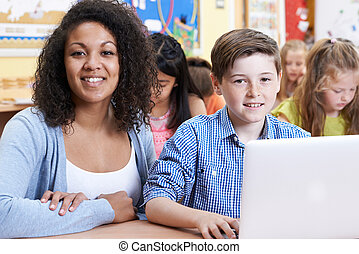 Teacher Helping Male Elementary Pupil In Computer Class