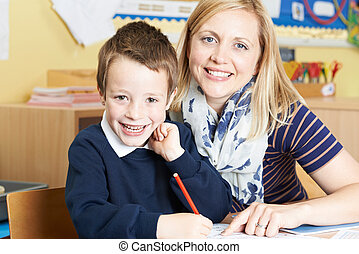 Teacher Helping Male Elementary Pupil Working At Desk