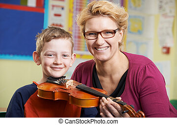 Teacher Helping Male Pupil To Play Violin In Music Lesson