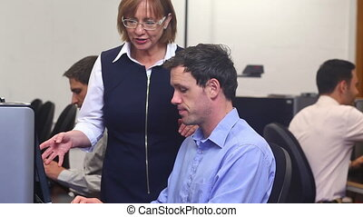 Teacher helping mature student in computer class at the ...