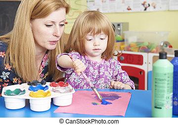 Teacher Helping Pre School Child In Art Class