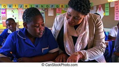 Teacher helping schoolchildren in a lesson at a township school 4k