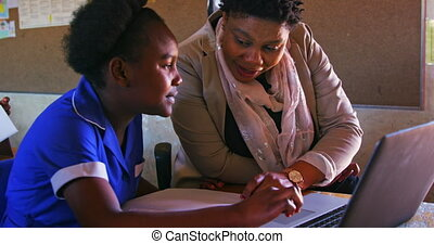 Front view close up of a middle aged African female school teacher helping a young African schoolgirl sitting at her desk using a laptop computer during a lesson in a township elementary school classroom, while beside her and in the background classmates are busy writing in their books 4k