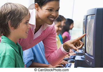 Teacher helping student at computer terminal with students...