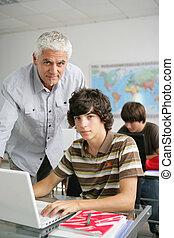 Teacher helping teen in class