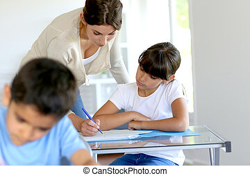 Teacher helping young girl in class with lesson