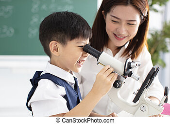 teacher helps child to conduct experiment with microscope