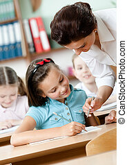 Teacher helps pupils to do the task - Young teacher helps...