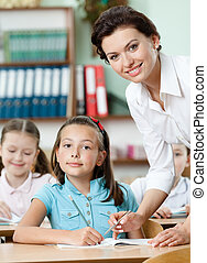 Teacher helps pupils to perform the task - Young teacher...