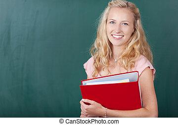 Teacher Holding Binder Against Chalkboard