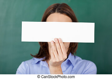 Teacher Holding Blank Paper Against Chalkboard
