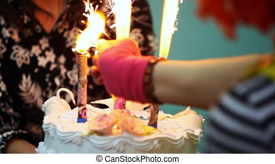 teacher holding cake with three fireworks, cute little girl happily claps