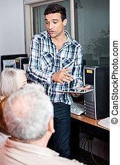 Teacher Holding Digital Tablet While Explaining To Senior Studen