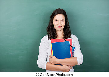 Teacher Holding Files Against Chalkboard - Portrait of young...