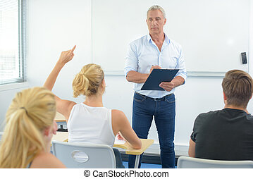 Teacher in front of class, student with arm raised