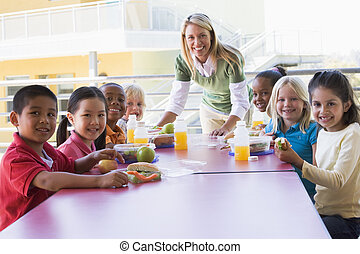 Teacher leaning on table outdoors while students eat lunch...