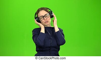 Teacher listening to music on headphones. Green screen -...