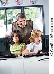 Teacher Looking At Schoolchildren Using Desktop Pc