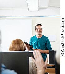 Teacher Looking At Student Raising Hand During Computer Class