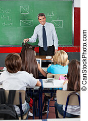 Teacher Looking At Students In Classroom