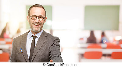 Teacher man using glasses holds hands welcoming in handshake pose, expressing trust and success concept, greeting