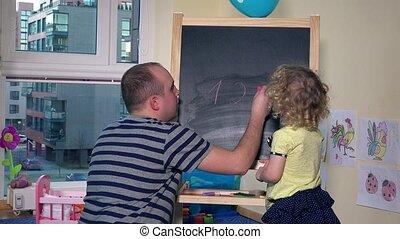 Teacher man writing numbers on chalk black board for little...