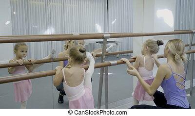Teacher near ballet shows young children dance position.