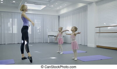 Teacher of children's dance school shows girls exercises in...