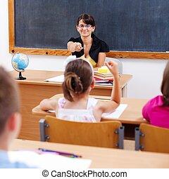 Teacher pointing at schoolgirl with raised arm