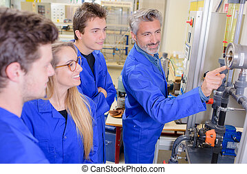 Teacher pointing to machine, everyone smiling