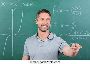 Teacher Pointing While Looking Away Against Chalkboard